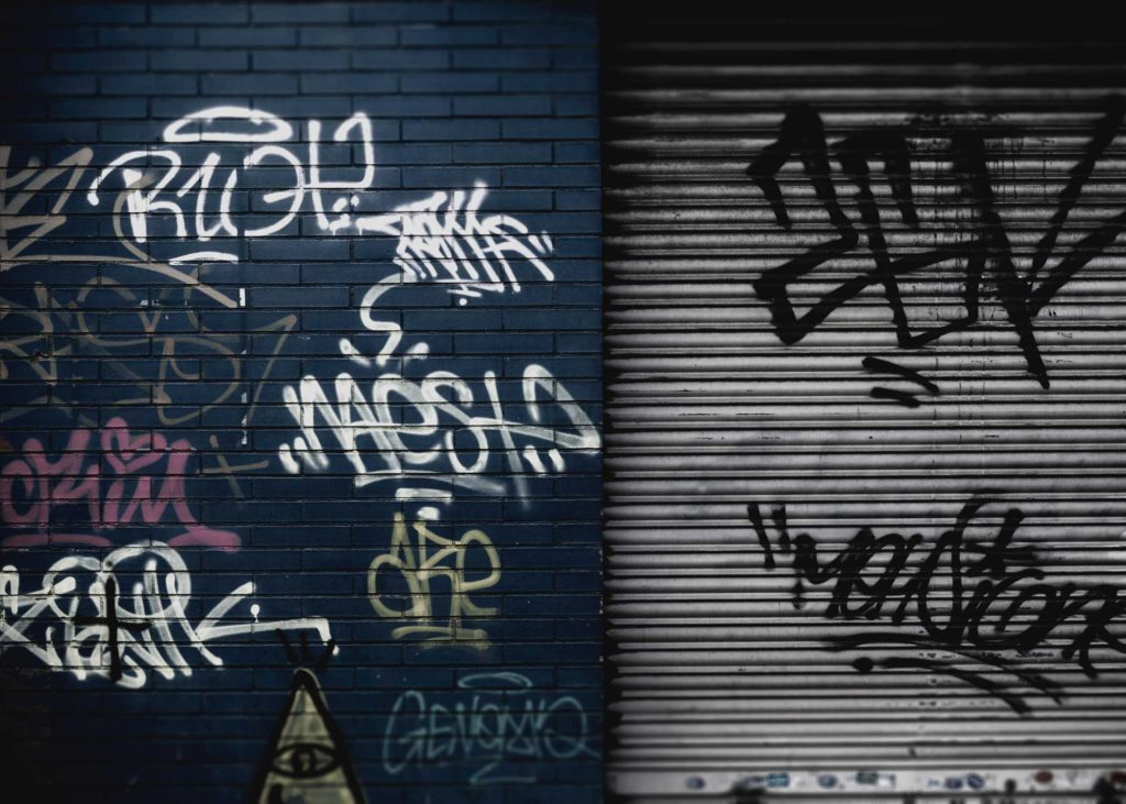 brick wall and steel door with graffiti