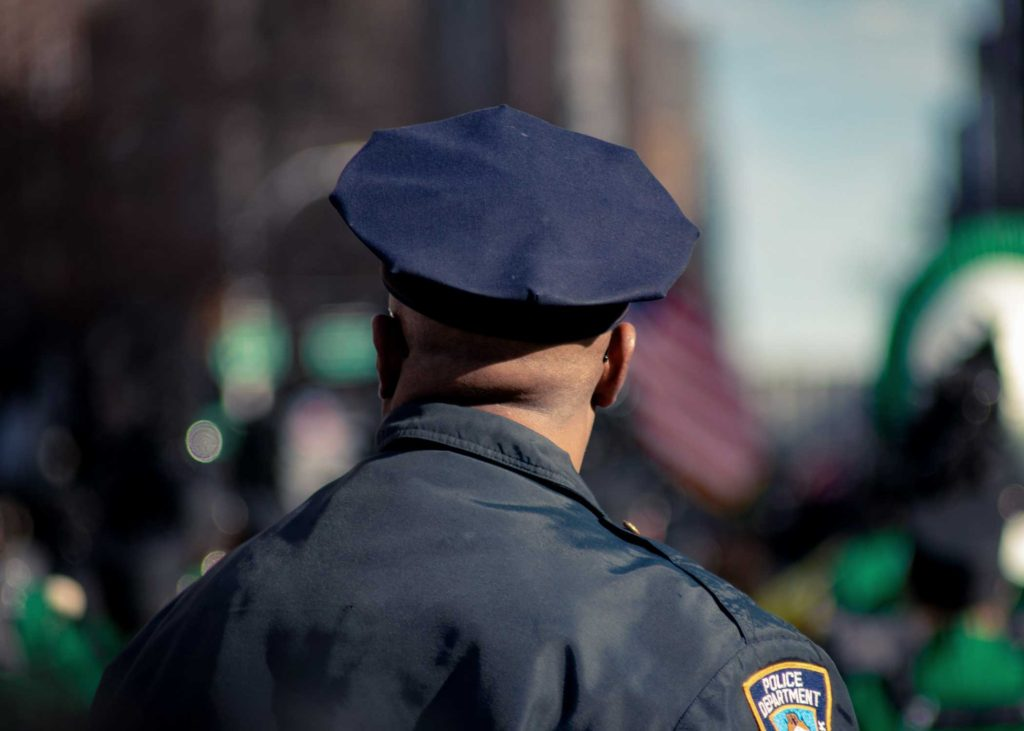 back of police man's head and shoulders in uniform